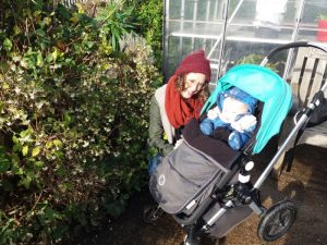 Woman and baby in front of a greenhouse